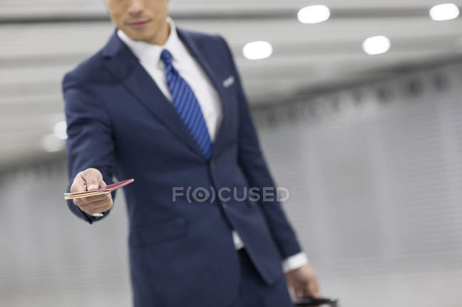 Businessman showing passport in airport — Stock Photo