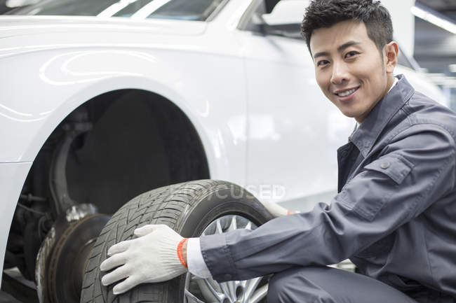 Chinese auto mechanic holding car wheel in workshop — Stock Photo
