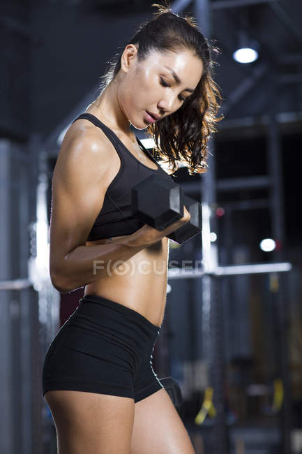 Chinese woman lifting dumbbell at gym — Stock Photo
