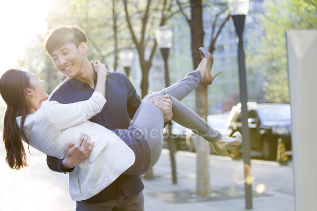 Chinese man carrying girlfriend in arms — Stock Photo