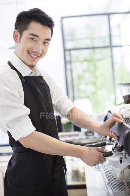 Barista standing at coffee maker and looking in camera — Stock Photo