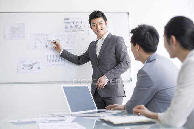 Chinese business people discussing strategy at whiteboard — Stock Photo