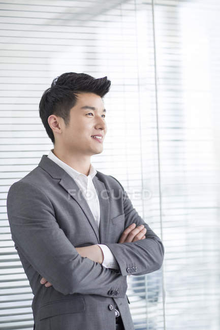 Chinese businessman standing in office with arms folded — Stock Photo