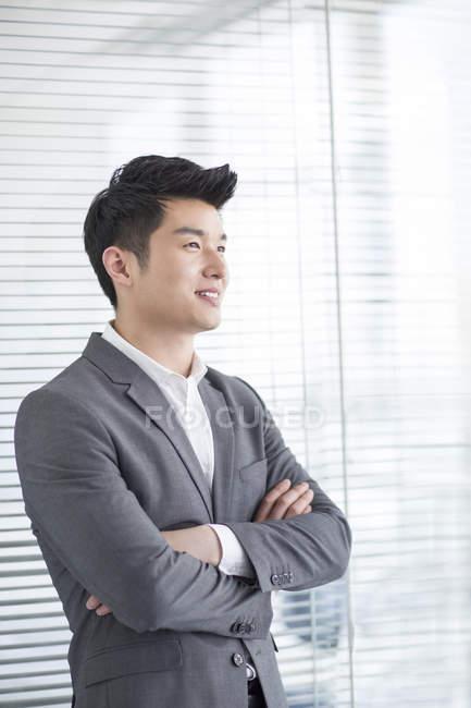 Китайский бизнесмен, стоя в офисе с сложив — стоковое фото