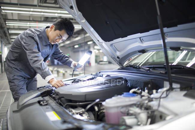 Chinese auto mechanic examining car engine — Stock Photo