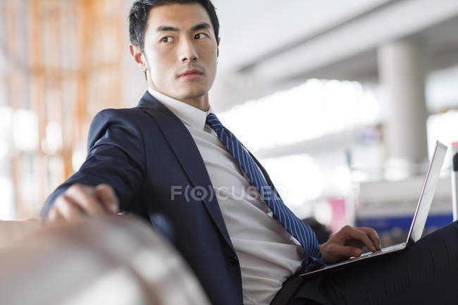 Chinese businessman sitting with laptop in airport waiting room — Stock Photo
