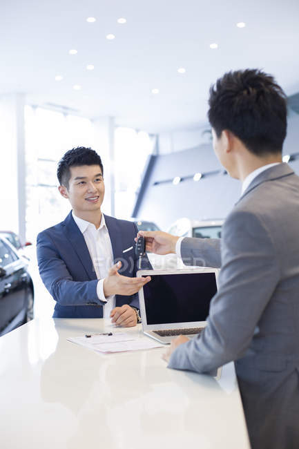 Chinese car dealer giving man car keys in showroom — Stock Photo