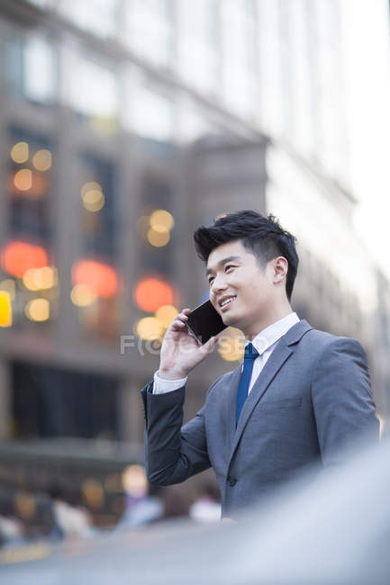 Chinese businessman talking on phone in city — Stock Photo