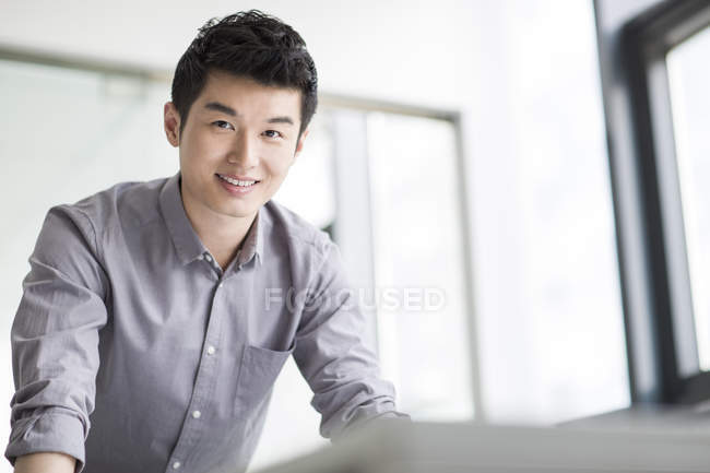 Chinese businessman leaning on table in office — Stock Photo
