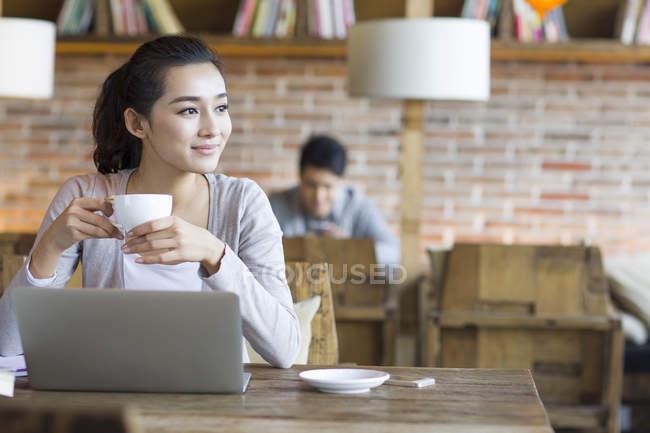 Donna cinese che si siede con il computer portatile e caffetteria in — Foto stock