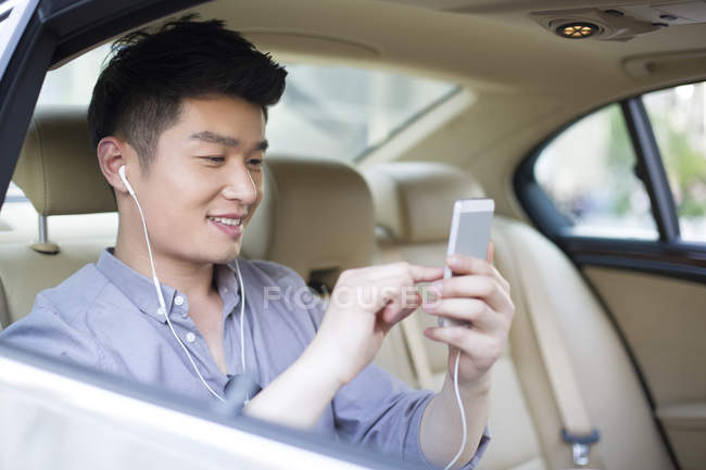 chinese man listening to music on car back seat selective focus