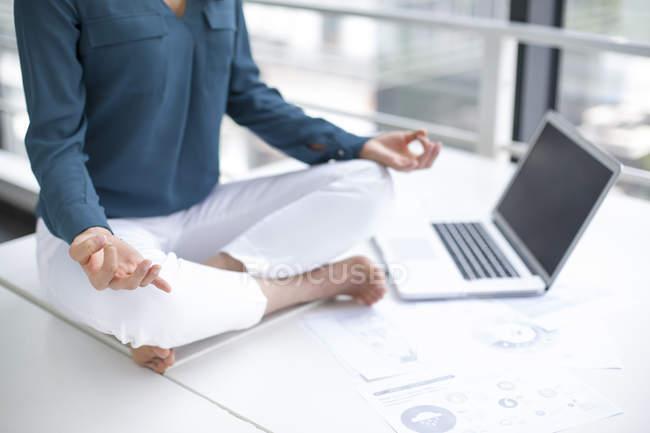 Donna che pratica yoga sul tavolo dell'ufficio — Foto stock