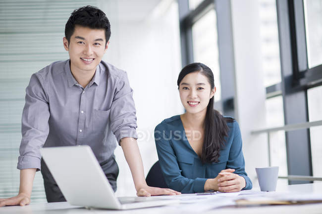 Chinese business co-workers at workplace looking in camera — Stock Photo
