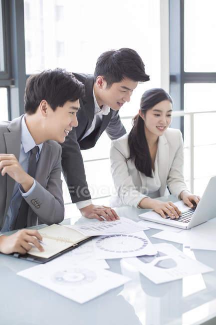 Chinesische Geschäftsleute mit Laptop bei treffen — Stockfoto