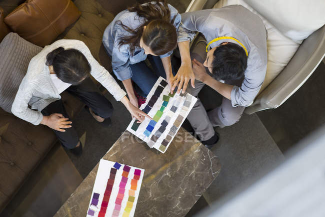Chinese fashion designers looking at textile samples in studio — Stock Photo