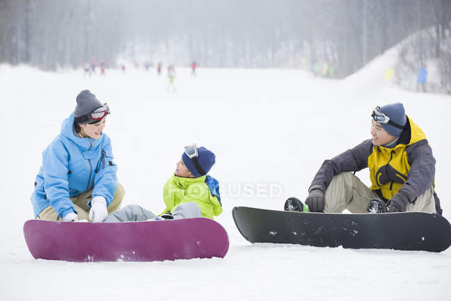 Chinese parents teaching son snowboarding — Stock Photo