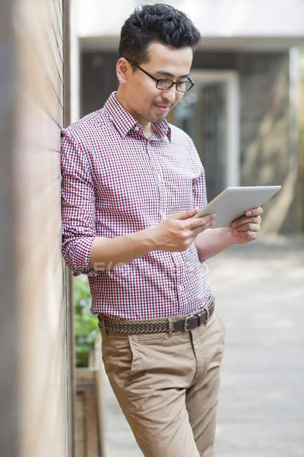 Homem chinês inclinado na parede e usando tablet digital — Fotografia de Stock