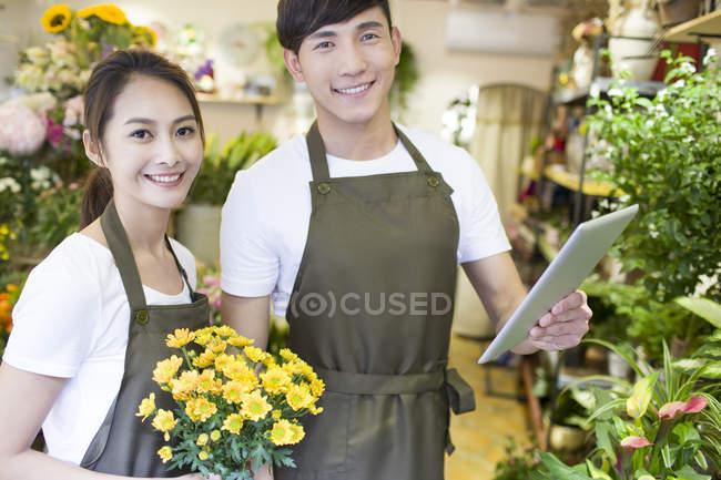 Китайские флористы стоят с цифровым планшетом в магазине — стоковое фото