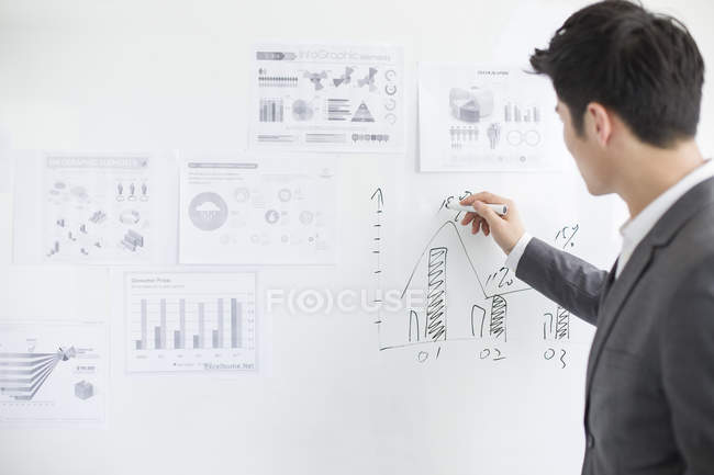 Businessman writing on whiteboard in office — Stock Photo
