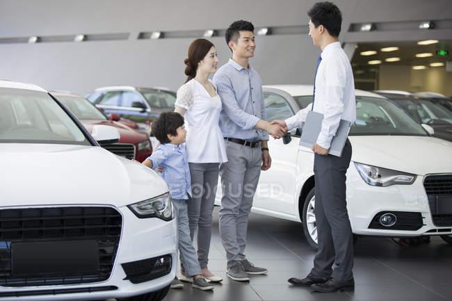 Китайські родини рукостисканням зі автомобіль продавець виставковий зал — стокове фото