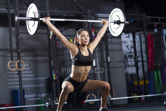 Chinese woman lifting barbell at gym — Stock Photo