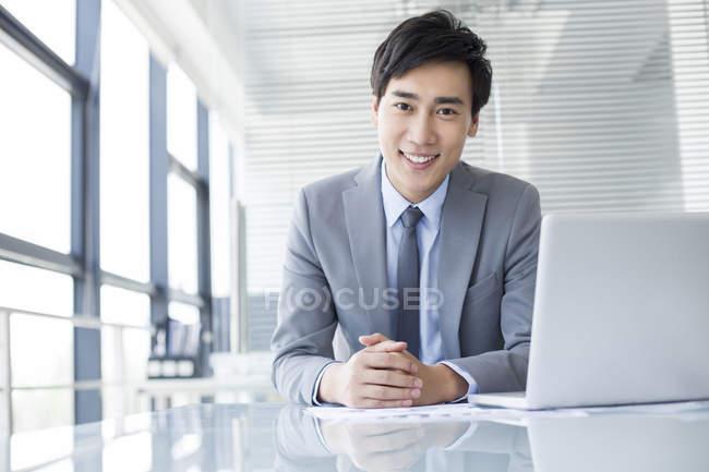 Uomo d'affari cinese seduto con computer portatile in ufficio — Foto stock