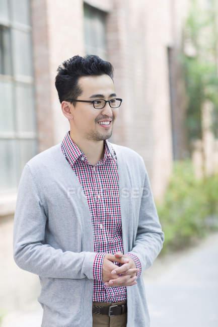 Uomo cinese in piedi con le mani strette — Foto stock