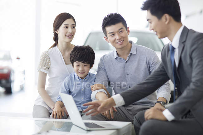 Chinese car dealer sitting with clients family in showroom — Stock Photo