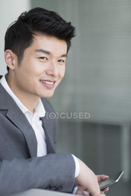 Ritratto di uomo d'affari cinese con smartphone — Foto stock