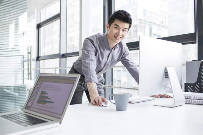 Uomo d'affari cinese che utilizza il computer in ufficio — Foto stock