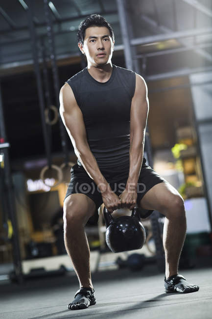 Chinese man entraînement avec kettlebell en crossfit gym — Photo de stock