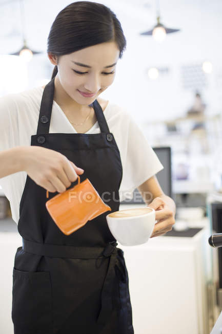 Chinese barista making cappuccino in cafe — Stock Photo
