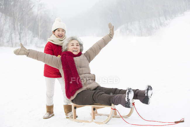 Chinese granddaughter pushing grandmother on sled — Stock Photo
