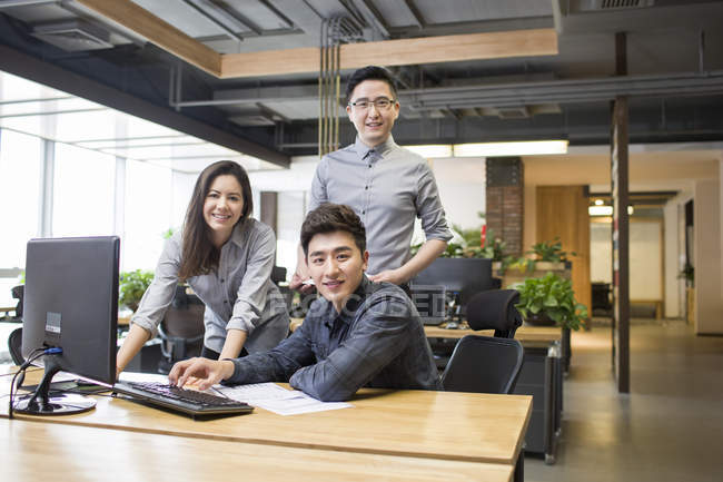 Chinese colleagues posing at desk in office — Stock Photo