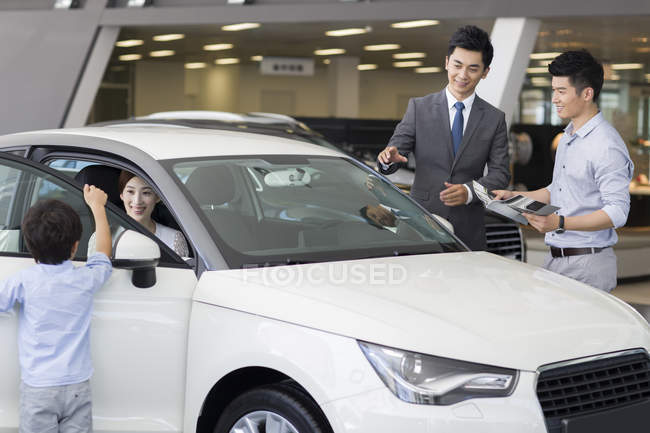 Chinese car dealer helping family choosing car in showroom — Stock Photo