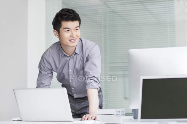 Китайский бизнесмен использует ноутбук в офисе — стоковое фото