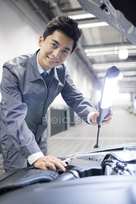 Chinese auto mechanic looking in camera while examining car engine — Stock Photo
