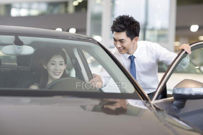 Китайська жінка, що прийняття тест-драйв з автомобіля дилером допомоги — стокове фото