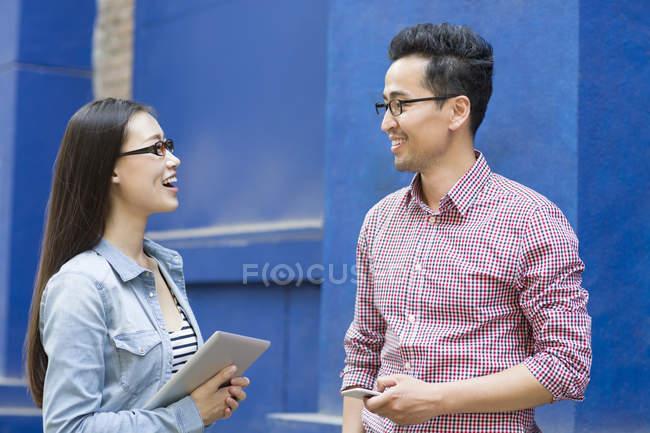 Китайские коллеги стоят и разговаривают на улице — стоковое фото
