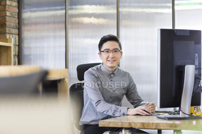 Travailleur informatique chinois assis sur le lieu de travail — Photo de stock
