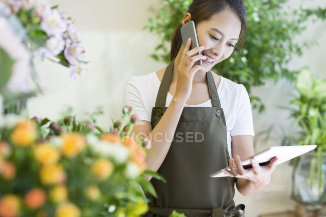 Chinese female shopkeeper talking on phone in shop — Stock Photo