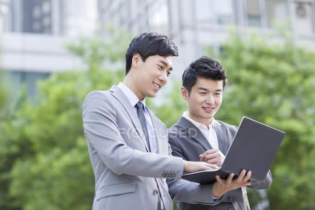 Collaboratori cinesi che lavorano con laptop in strada — Foto stock