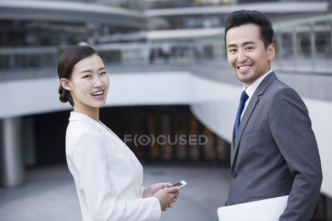 Chinese business people standing on street with laptop and phone — Stock Photo