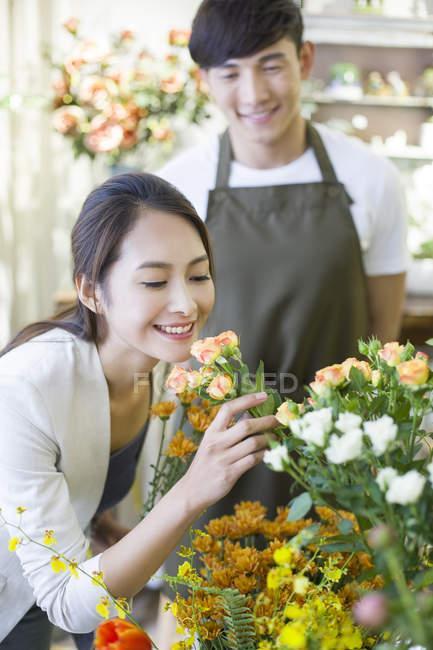Китайська жінка, що пахнуть троянди в магазин з флорист — стокове фото