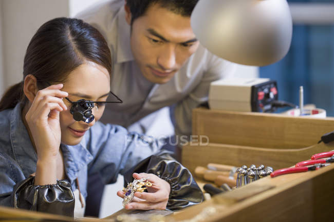 Chinese jewelers examining jewelry with loupe — Stock Photo