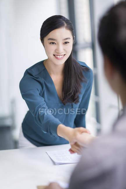 Китаянка пожимает руку бизнесмену — стоковое фото