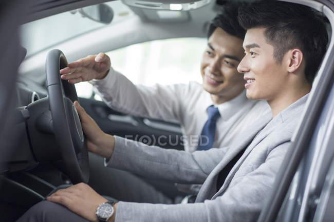 Дилер автомобілів, допомагаючи людині з тест-драйв — стокове фото