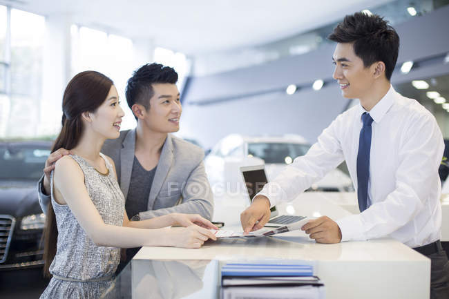 Chinese couple buying car in showroom — Stock Photo