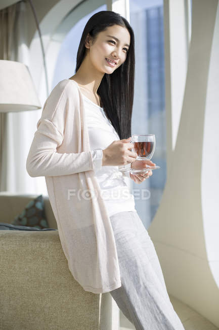 Chinese woman holding cup of black tea in home interior — Stock Photo