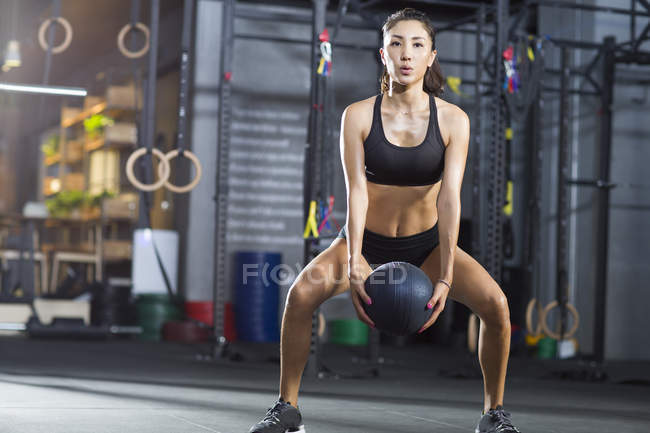 Chinese woman exercising with medicine ball at gym — Stock Photo